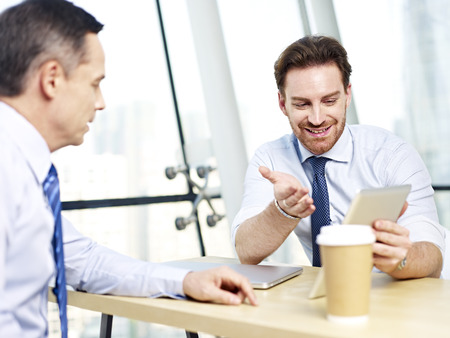 appraising: two caucasian office people discussing business using tablet computer in office. Stock Photo