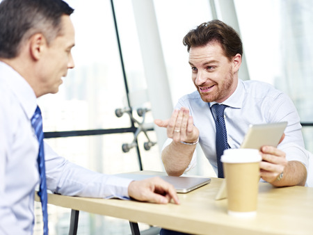 review: two caucasian office people discussing business using tablet computer in office. Stock Photo