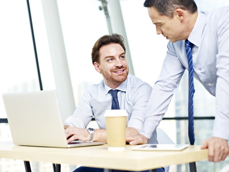 patron: dos personas de raza blanca de oficina que trabajan juntos usando la computadora portátil en la oficina.