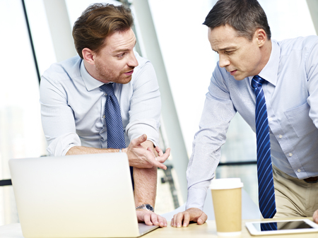 westerner: two caucasian business executives working together using laptop computer in office.