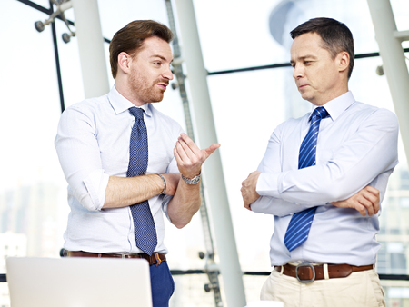 corporate office: two caucasian business persons standing and chatting in office. Stock Photo