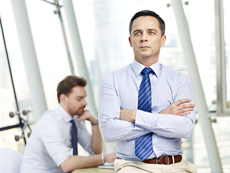 westerner: caucasian businessman sitting on desk arms crossed thinking contemplating in office with colleague in background. Stock Photo