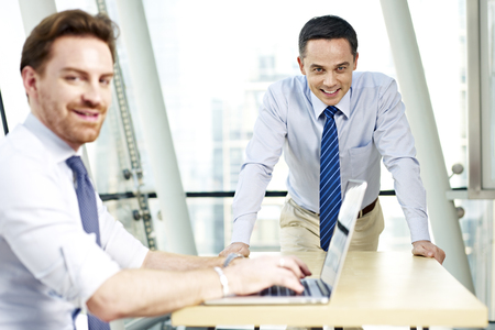 westerner: two caucasian business executives working in office looking at camera smiling.