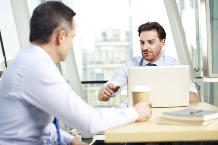 appraising: two caucasian business men having a conversation in office. Stock Photo