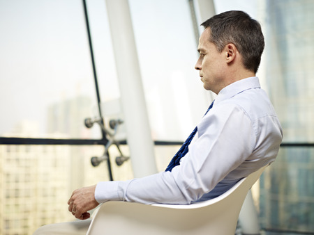 dudando: caucasian business executive sitting by the window in a chair thinking in office.