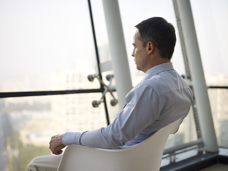man looking out: caucasian business executive sitting by the window in a chair thinking in office.