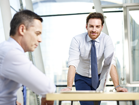 westerner: two caucasian corporate people working in office looking at camera smiling.