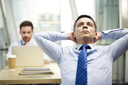 hard day at the office: caucasian businessman sitting in office hands behind head thinking with colleague working in background.