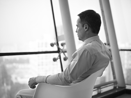 indecisiveness: caucasian business executive sitting by the window in a chair thinking in office, black and white.