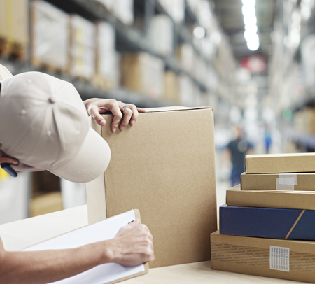 replenishing: warehouse worker checking and recording goods received or to be shipped out. Stock Photo