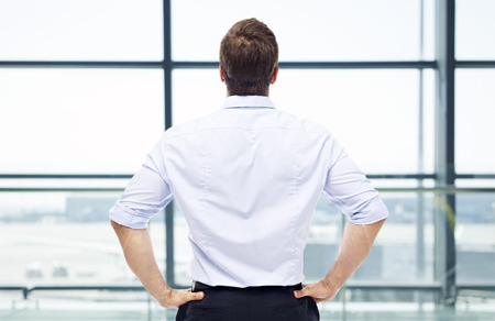 rear view of a caucasian man standing by the window looking out and thinking in a modern airport. Stock Photo