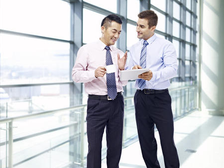 two businessmen, one asian and one caucasian, having a discussion while waiting for flight at airport. Stock Photo