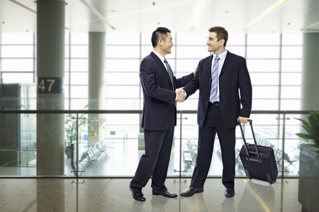 arrival: two businessmen, one asian and one caucasian, shaking hands and smiling at modern airport.