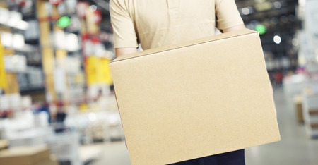 warehouseman: male warehouse worker carrying a carton box of goods in a cash & carry wholesale store.