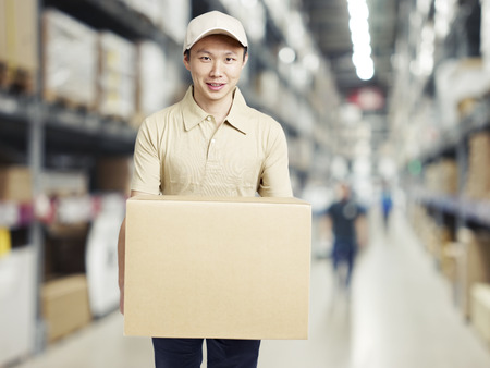 replenishment: male warehouse worker carrying a carton box of goods in a cash and carry wholesale store. Stock Photo