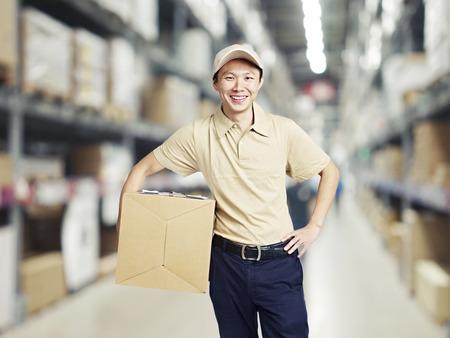 obrero trabajando: retrato de un trabajador de almacén joven sonriente que trabaja en un cash and carry almacén al por mayor. Foto de archivo