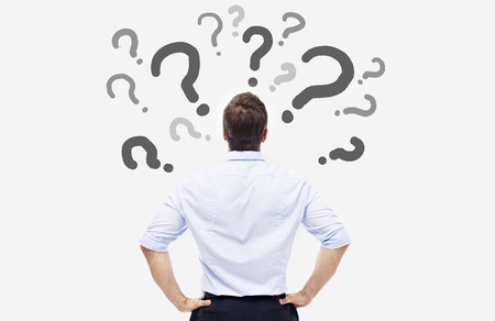punto interrogativo: vista posteriore di una persona di affari caucasica guardando la interrogativi sulla scheda bianca.
