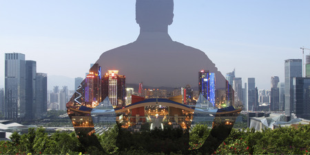 superimposed: silhouette of a man superimposed on a panorama view of a modern city.