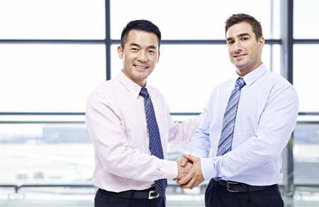 two businessmen, one asian and one caucasian, shaking hands looking at camera at modern airport.