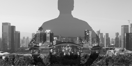 silhouette of a man superimposed on a panorama view of a modern city, black and white.