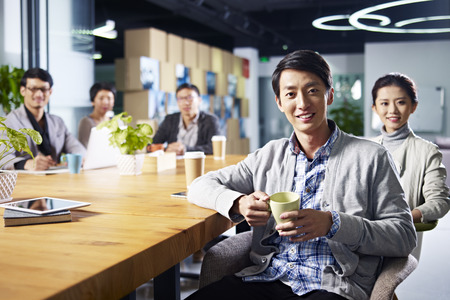 peers: a team of young asian entrepreneurs posing in meeting room.