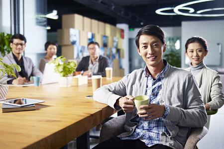 une équipe de jeunes entrepreneurs asiatiques posant dans la salle de réunion.