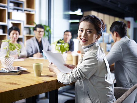 peers: young asian designer business woman looking at camera smiling during meeting. Stock Photo