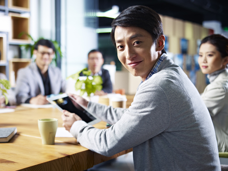 młodych asian projektant człowiek biznesu patrząc na kamery uśmiecha się podczas spotkania.