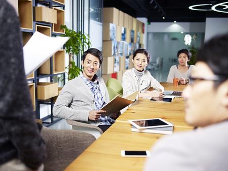 若いアジアの起業家オフィスの新しいビジネスのためのアイデアを議論する会議のチーム。