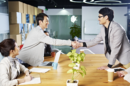 negotiation business: young asian business people shaking hands smiling before meeting or negotiation