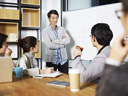 facilitating: young asian business executive facilitating a discussion or brainstorm session in meeting room.