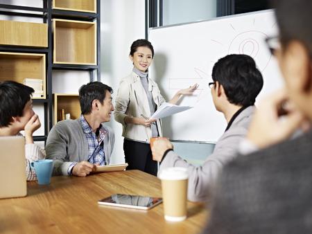 회의실에서 토론 또는 브레인 스토밍 세션을 촉진 젊은 아시아 비즈니스 임원.