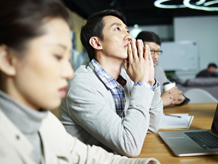 hoping: young asian businessman looking up and thinking during meeting in office. Stock Photo