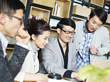 a team of young asian entrepreneurs working together using laptop computer in office. Stock Photo