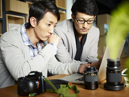 hombres jovenes: Dos fotógrafos asiáticos que miran la computadora portátil con la expresión facial seria.