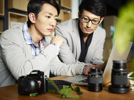 korean man: two asian photographers working together selecting images using laptop computer.