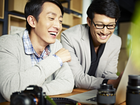 two asian photographers working together selecting images using laptop computer, happy and laughing. Stock Photo