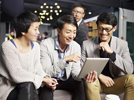 jóvenes hombres de negocios asiáticas que se sientan en el sofá mirando la computadora de la tableta, feliz y sonriente.