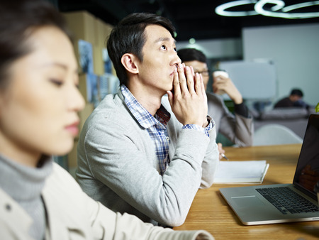 korean man: young asian businessman looking up and thinking during meeting in office. Stock Photo