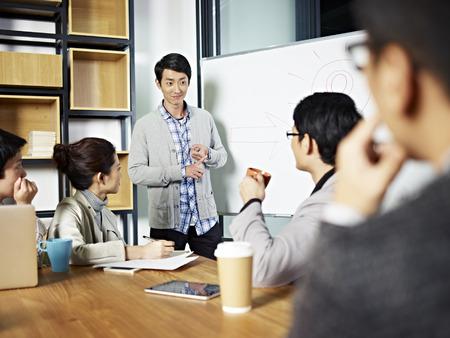 preguntando: joven empresario asiático facilitar una discusión de grupo o de formación en el cargo. Foto de archivo