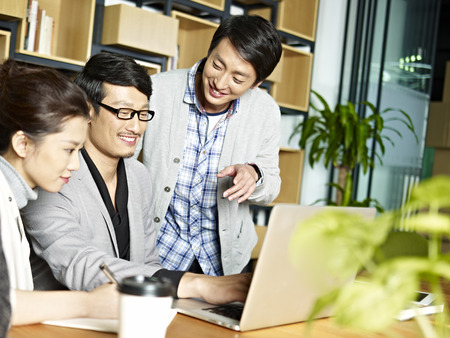 a team of young asian business people working together using laptop computer in office. Stock Photo