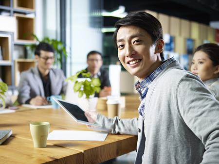 comité d entreprise: jeune confiant affaires asiatique tournant à regarder appareil photo lors de la réunion dans le bureau.