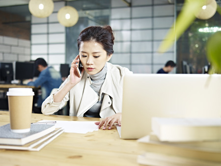 Jonge Aziatische kantoormeester zittend op bureau bellen met behulp van mobiele telefoon in kantoor.