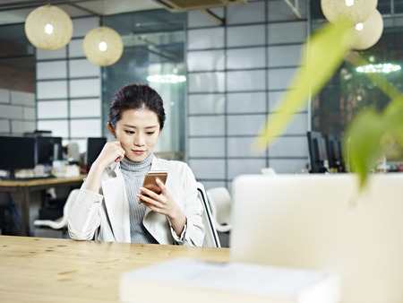 young asian office worker sitting at desk looking at cellphone in office.