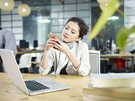 messaging: young asian office worker sitting at desk playing with cellphone in office.