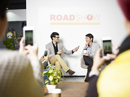 interviewed: young asian entrepreneur being interviewed while the audience taking pictures using cellphone during roadshow.