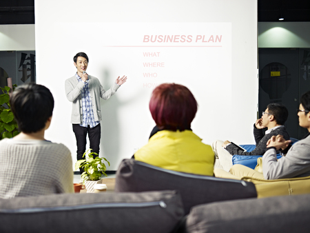 office presentation: young asian entrepreneur presenting business plan for new project.