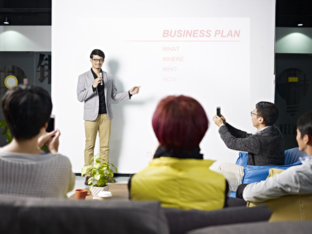 若いアジア起業家の視聴者と携帯電話で写真を撮る新しいプロジェクトのためのビジネス プランを提示します。 写真素材