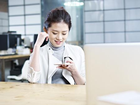 jonge Aziatische kantoor vrouw kijken naar mobiel en glimlachen.