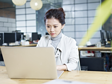 woman hard working: young asian business woman working in office using laptop computer. Stock Photo